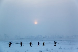 Image showing a team of people walking across snow